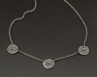 a triplet sand dollar necklace in silver