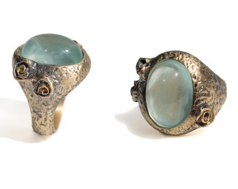 statement gold ring with large oval aquamarine cabochon and carved roses