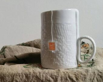 Handmade ceramic mug with impression of a vintage doily.  Pale gray ceramic mug.  Porcelain mug with abstract floral pattern.