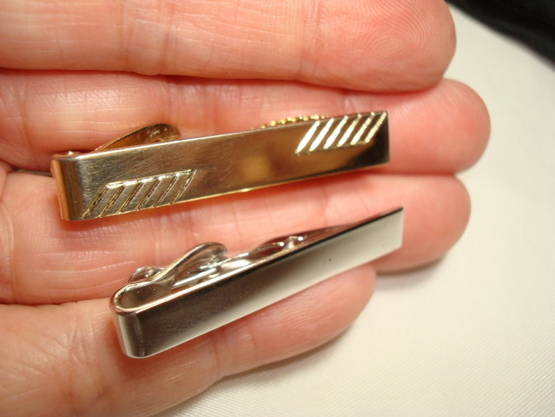 Two Vintage Tie ClipsClasp One in Gold Tone and One in Silver Tone.