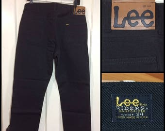 1960s deadstock Lee Riders tapered leg jeans size 34, measures 33x30 black denim Sanforized side label Union made in USA hard plastic patch