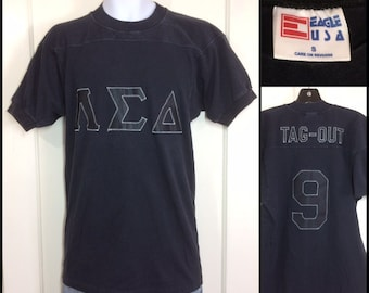 1970s Lambda Sigma Delta LSD fraternity football jersey style t-shirt size small 17x28 black heavy cotton sewn appliquéd letters Tag-Out 9