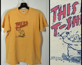 "1980s 1983 Humor ""This is a T-shirt"" graffiti cartoon artist E. Smith size Large 20x24 all cotton yellow"