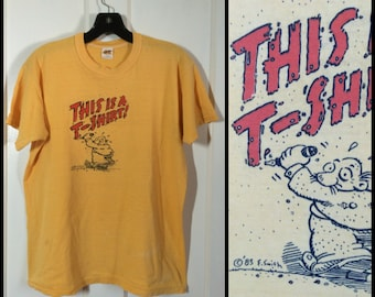 "Vintage 1980's 1983 Humor ""This is a T-shirt"" graffiti cartoon artist E. Smith size Large 20x24 all cotton yellow"