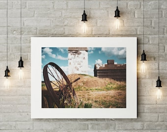 Photograph of Rusty Wheel Sitting in Field with a Alberta Pacific Grain Elevator printed on Fine Art Paper
