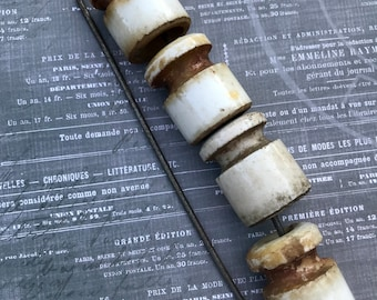 Four Vintage Ceramic Porcelain Insulators Displayed On A Laundry Pin