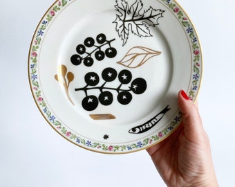 Antique plate screenprinted with tomatoes, pasta and anchovies in black and gold, illustrated by Celinda.