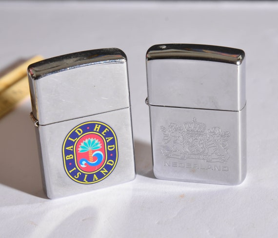 Two vintage 1990s Zippo Lighters  One Bald Head ISland and one Nederlands Netherlands Engraved