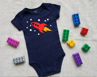 Space ship and space shirt. Rocket ship. Bodysuit. Stars. Red. Blue. Navy. Yellow. White. Little Fawn Lane.