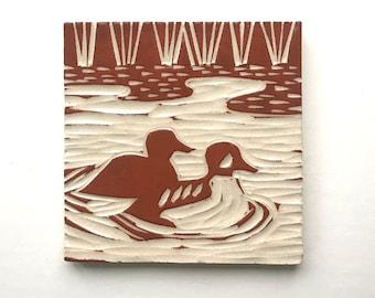 "Mergansers swimming in wetlands, 4"" x 4"" hand carved terra-cotta and white tile, linoleum block look"