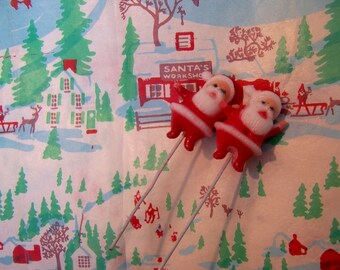 two tiny wee santas on a wire