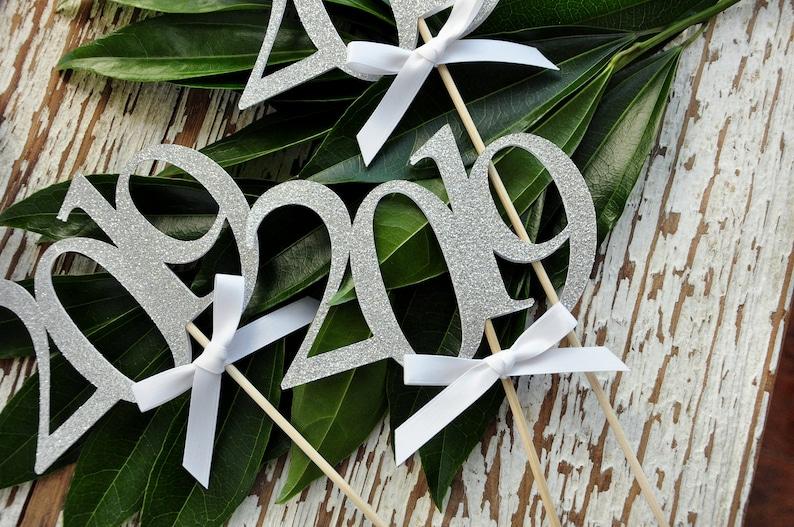2019 Centerpiece. Graduation Centerpiece Silver 2019 Graduation Centerpiece Sticks with White Bows. 3 Single- 2019 Wands