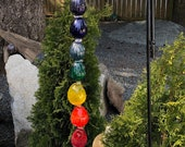 Outdoor Chakra inspired Garden Bell.  Made of blown glass in a rainbow of a colour and a working brass bell.