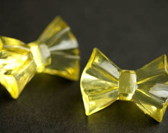 Two (2) Yellow Bow Buttons. Yellow Buttons. Bow Tie Buttons. Clear Buttons. Clear Acrylic Buttons. Clear Plastic Buttons. 19mm x 25mm