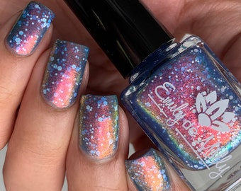 """Nail polish - """"Blessed With A Curse"""" A pale dusty blue with a pink / orange / gold / green shifting shimmer and white glitter"""