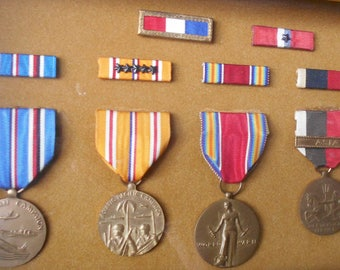 A collection of a WWII Soldier's Medals in Wall Display Case.