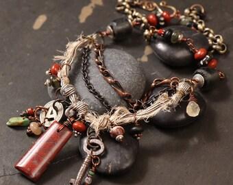 Traveler multi strand necklace: red jasper pendant, vintage skeleton key and subway token, sari silk ribbon, African black recycled glass