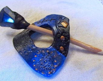 Lapis Lazuli faceted stone on top of a Red Oak stick and a blue and black shawl/scarf pin