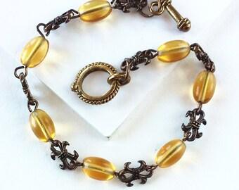 Golden Fleur de Lis Brass and Glass Bead Bracelet