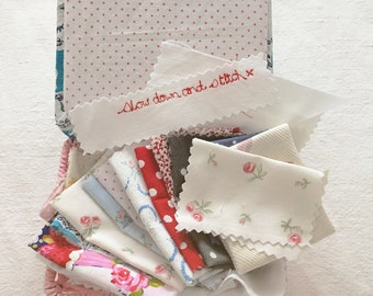 Vintage sewing basket with a collection of vintage fabric pieces for patchwork and applique: pink, red,  blue + embroidered words