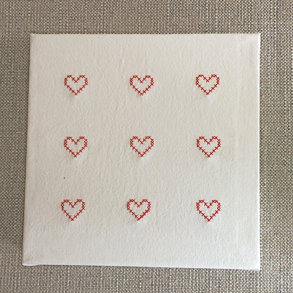 Canvas with embroidered tiny red cross stitch hearts on white vintage linen