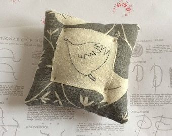Generous size, plump pincushion. All linen with vintage touches and embroidered bird.