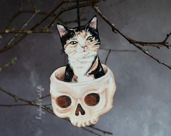 Cat in a skull Halloween decoration. Wooden hanging decoration. Marmalade the tortoiseshell cat