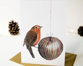 Christmas card of a robin redbreast and a decorative red and green apple. Christmas art. Seasonal card. Card for a friend.