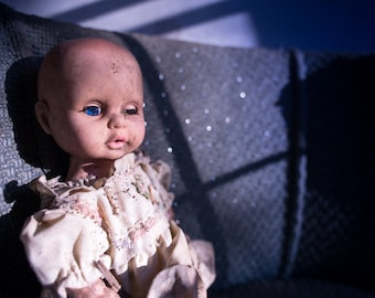 8x10 Signed Archival Photographic Print of a Creepy Baby Doll in an Abandoned house on a Blue Chair with window shadows
