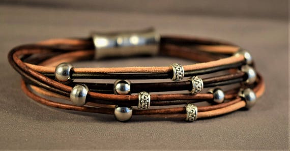 Women leather bracelet with different browns strings of leather and stering silver and stainless steel beads