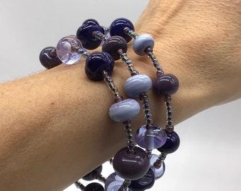 Mauve and shades of purple glass bead bracelet. 31 handmade lamp work glass beads on a memory wire bracelet