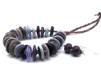 Mauve and grey glass disc necklace. 31 handmade lamp work beads in shades of purple and green grey transparent and opaque glass