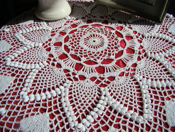White crocheted pineapple popcorn stitch table topper with crochet hearts and scalloped edging