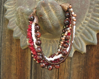 7 strand bracelet in  dramatic colors of reds, browns and creams with copper cones and copper chain extension.