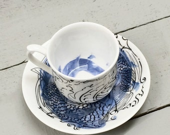 Wave and koi inspired blue black and white bone china cup and saucer