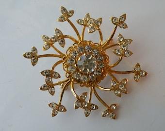 On Sale Pinwheel, snowflake brooch, pin. Clear rhinestone, gold tone metal.