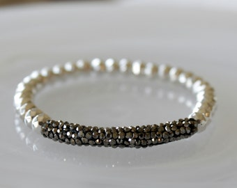 Beaded Stretch Bracelet with Silver Faceted metal beads and a pave rhinestone tube embellishment.