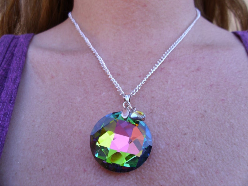 Single stand necklace with a green hue iridescent  pendant with vintage small heart