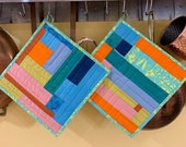 Pair of modern quilted potholders in crazy brights