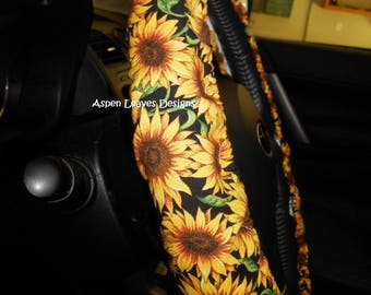 Sunflower Steering wheel cover. Yellow and gold sunflowers with green leaves on black. Seat belt covers and key fob options.