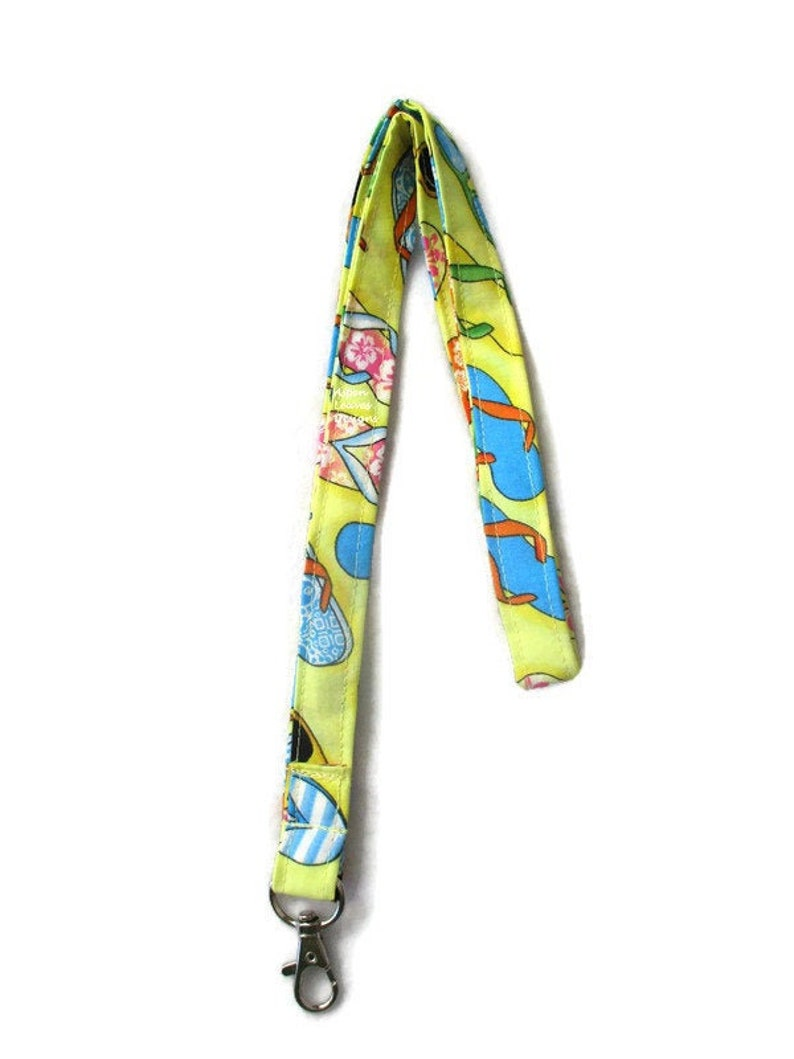 Flip flop lanyard. Sunglasses and summer flip flops on yellow. image 0