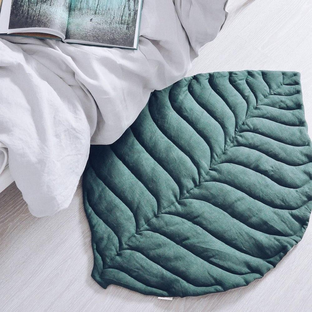 A green linen leaf-shaped play mat from OMOLOKO