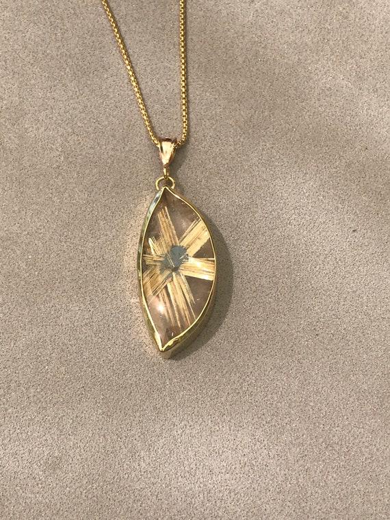 Rutilated quartz in 18k gold pendant