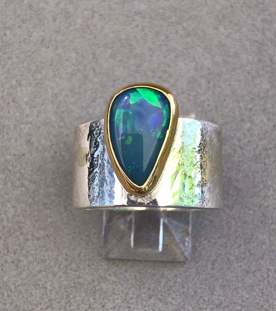 Opal doublet ring set in a 22k gold bezel on a wide silver band