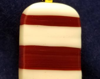 Fused glass strip pendant in an eye catching and stand out color combination. Shaped rectangle has rounded corners.