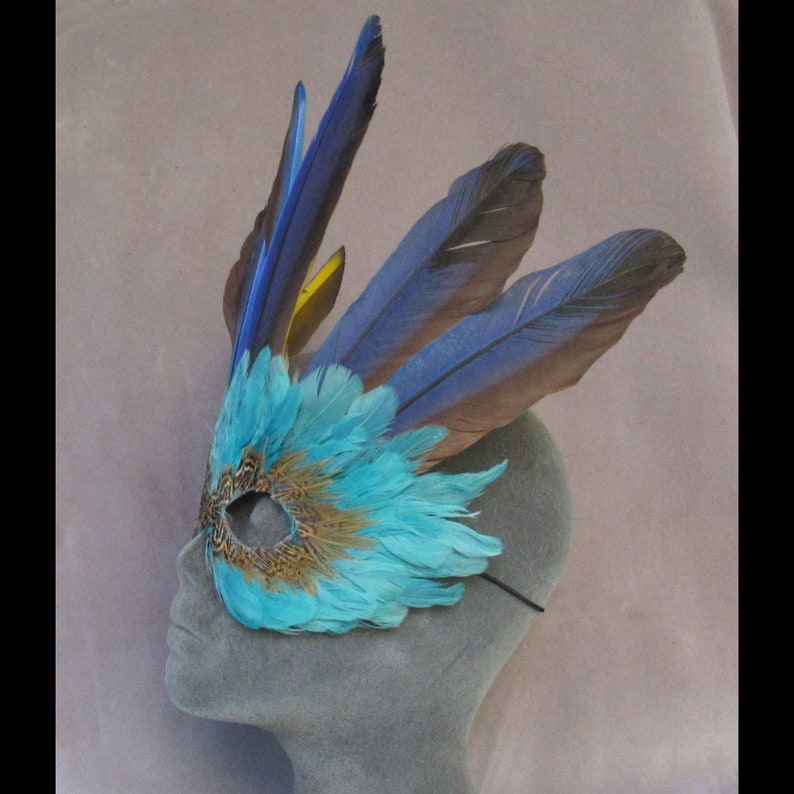 Turquoise Feather Mask Crowned by Macaw Feathers to become a fantasy character at a party or parade