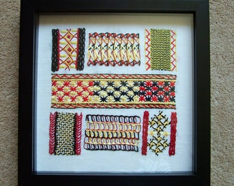 Embroidery sampler in red, yellow and black.