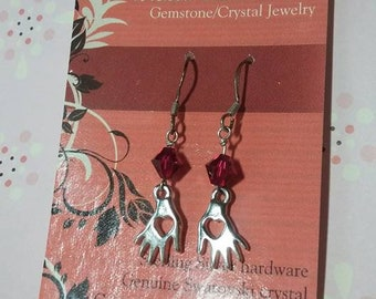 Swarovski crystal accented caring hands earrings, hot pink color, sterling silver earhooks.