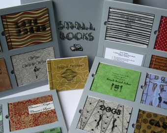 """Small Books: 16 Hand-made, """"Artisan"""" Books Inset in Framed Pages, Thumb Holes for Easy Retrieval, Housed in a Reinforced Clamshell Box"""