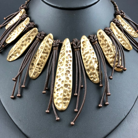 Hand sculpted dimpled bronze pods with leather fringe